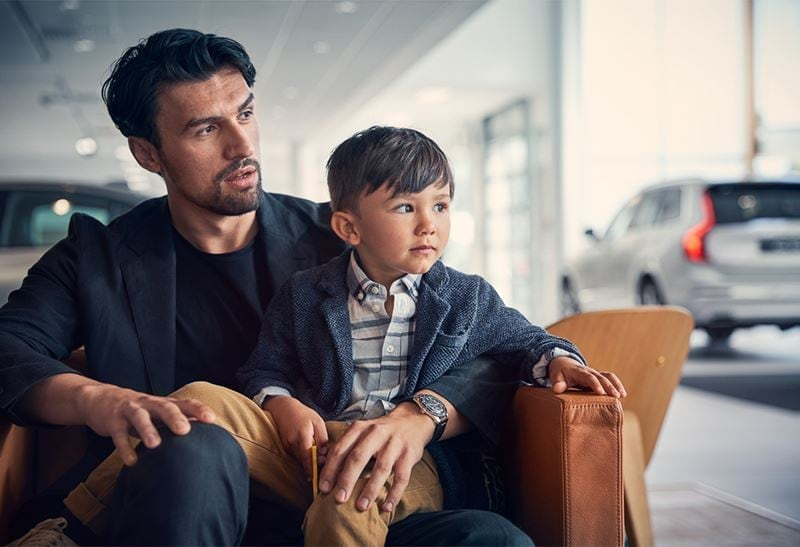 Man with boy on lap waiting for volvo maintenance